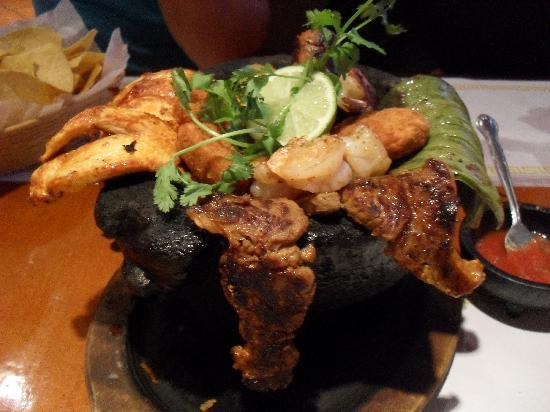 A volcanic stone made dish FILLED with Grilled Cactus, Chicken, Steak, Shrimp, Scalion, Viajero Chee - Molcajete at San Lucas Mexican Restaurant