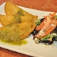 A spinach and cheese, beef, and chicken Colombian empanada topped with roasted tomatillo salsa. - Colombian Empanadas at Roots Gourmet